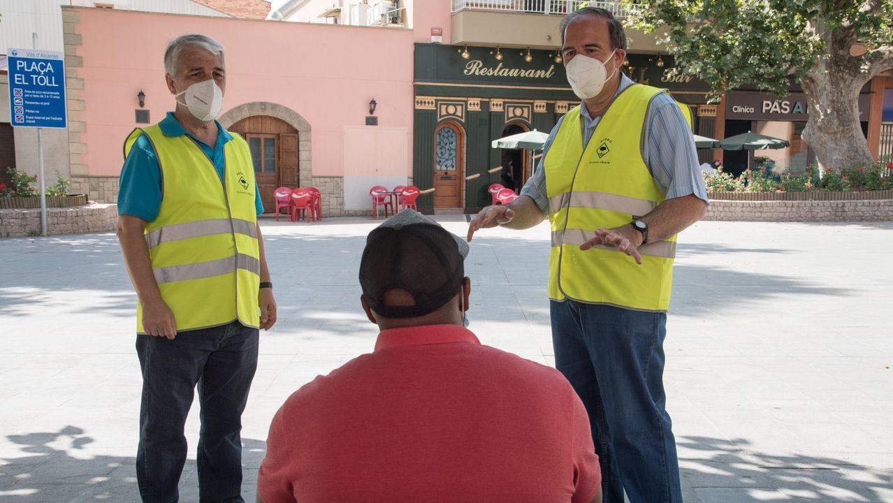 Dos agentes cívicos informan a un ciudadano de la obligación de usar la mascarilla en Lérida