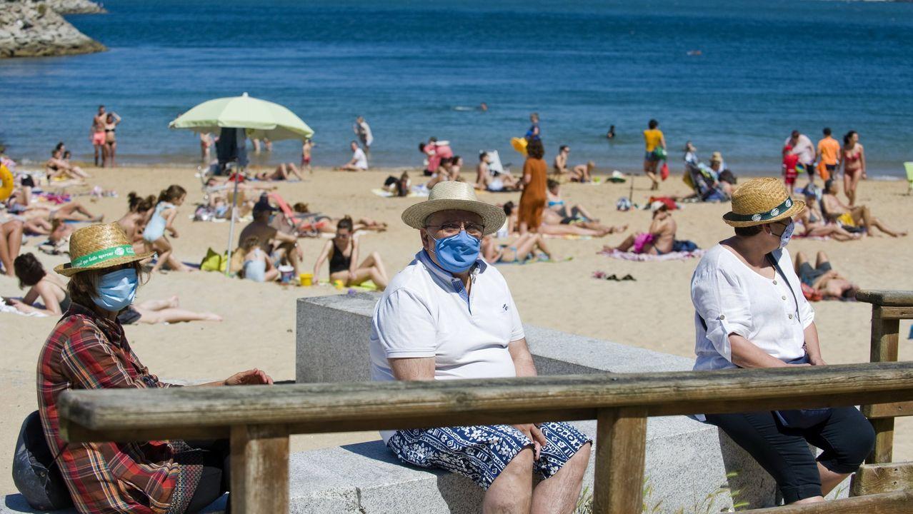 Bañistas con mascarilla en un arenal coruñés