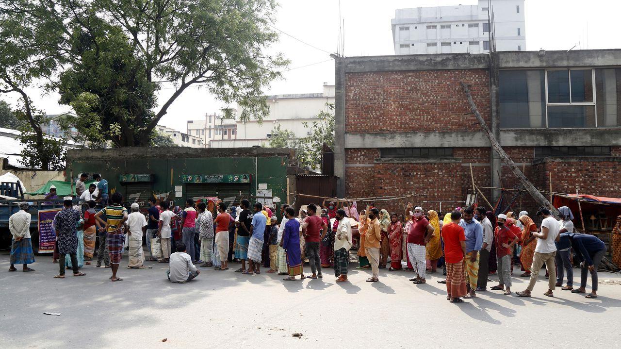 La gente de Bangladesh hace cola, algunos con máscaras protectoras, para comprar alimentos esenciales en una calle de Dhaka, Bangladesh