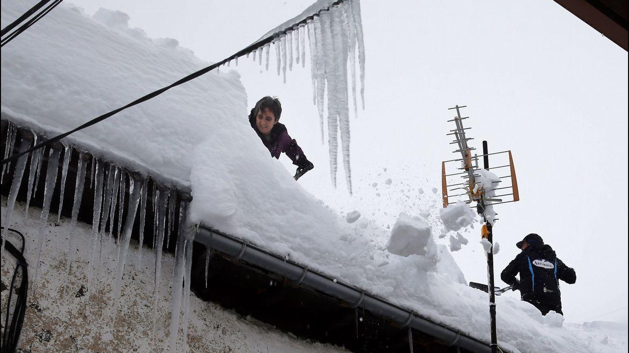 Carretera abierta alrededor de la nieve en Somiedo. Vecinos de Pajares (Asturias) retiran nieve del tejado de su casa de 300 años, una de las más antiguas del pueblo.