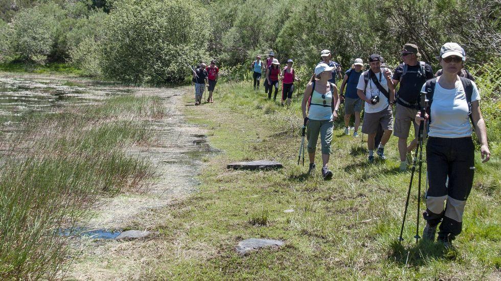 Miembros del club Senderismo Morrazo caminando por la orilla de la laguna