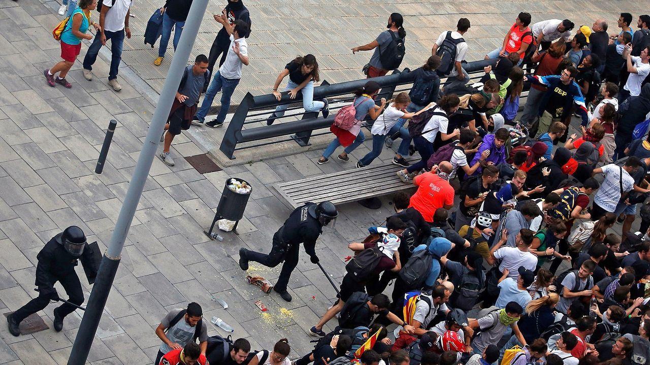 Miembros de los Mossos cargan contra centenares de personas que se agolpaban el lunes en Aeropuerto de El Prat