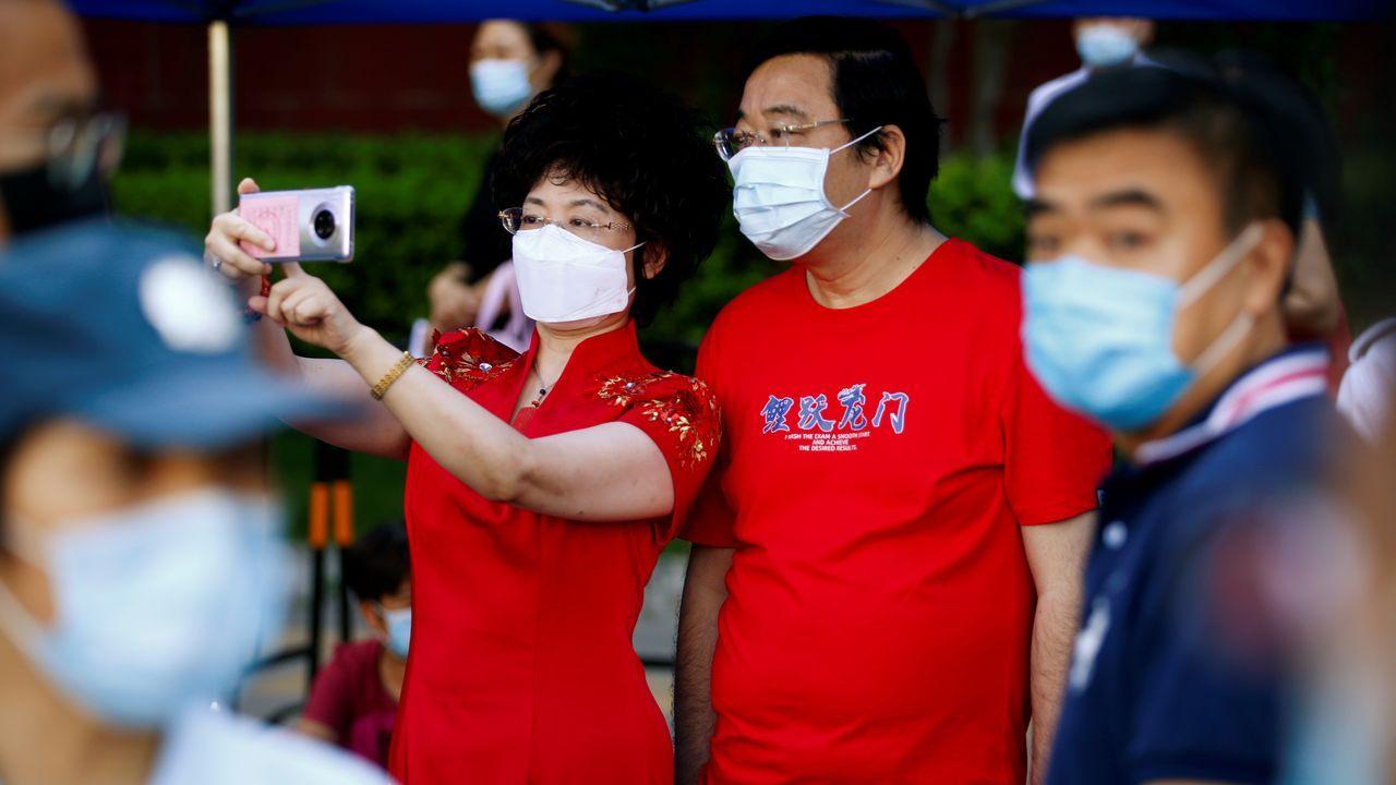 Padres esperan a la salida de un colegio de Pekín donde se realizan los examenes de admisión a la universidad, que habían sido postergados por el coronavirus