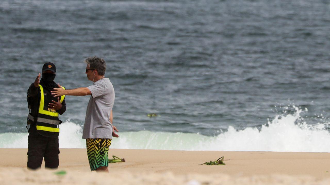 Un policía obliga a un bañista a abandonar una playa en Río de Janeiro