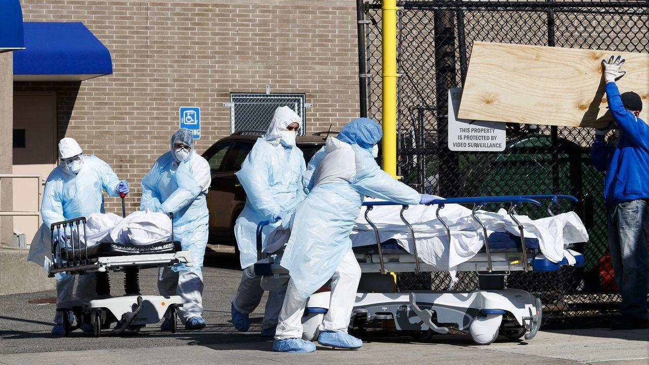 Unos empleados transportan dos cuerpos de personas fallecidas por coronavirus hacia una morgue temporal en el Centro Médico Wyckoff Heights  en el barrio neoyorquino de Brooklyn