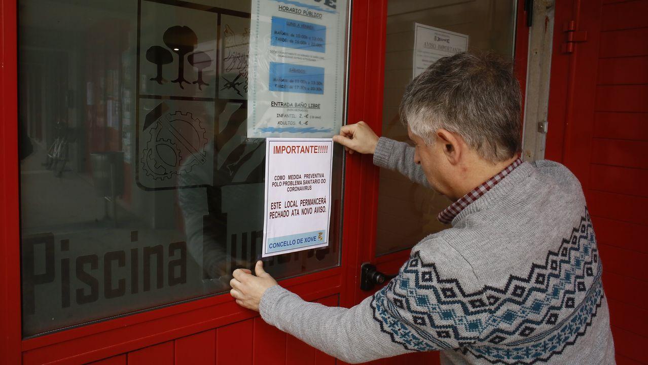 Imagen en Xove, donde un operario municipal coloca un cartel avisando del cierre la piscina municipal atendiendo a los consejos ante el estado de alarma
