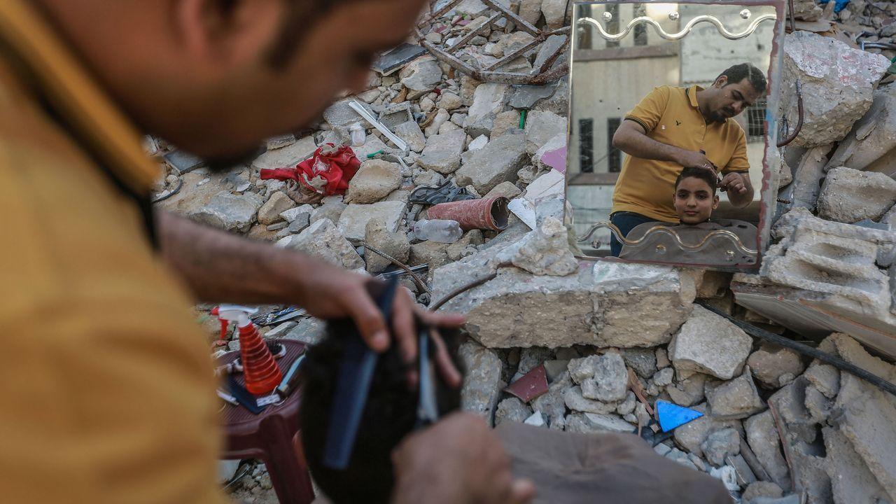 Un palestino corta el pelo a un niño entre las ruinas de un edificio en Gaza