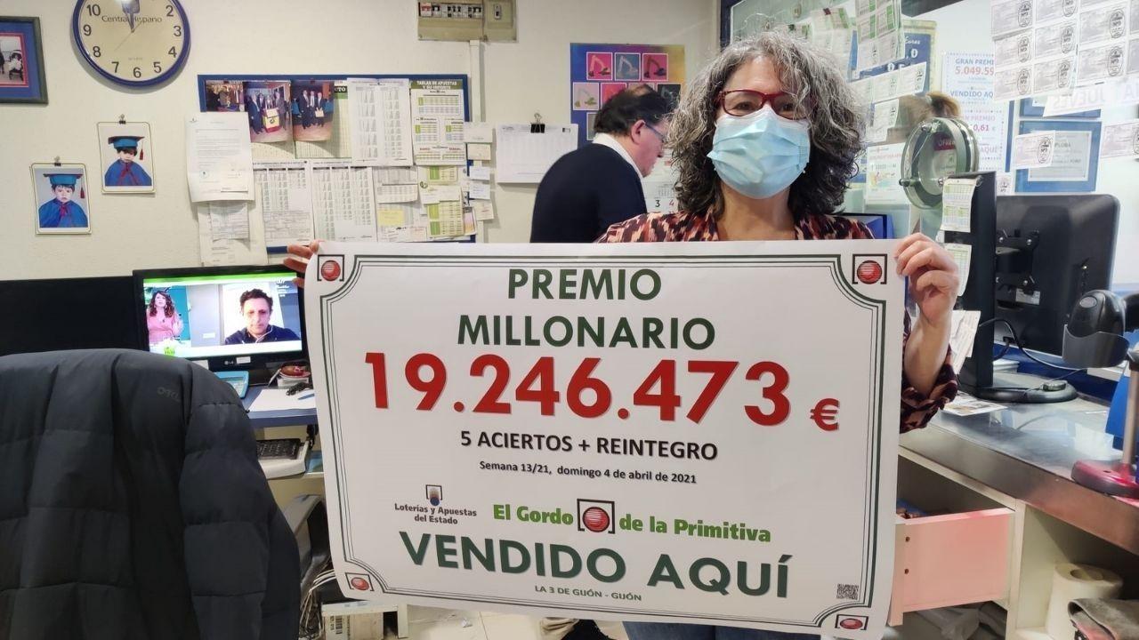 Amalia López Tuya posa junto al cartel del billete premiado