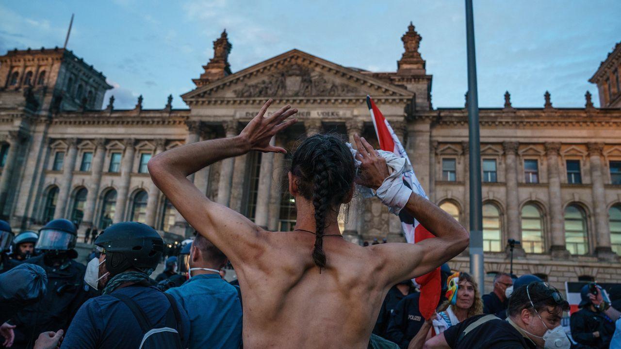 Un hombre levanta los brazos cuando la policía comienza a detener a manifestantes de extrema derecha frente al edificio del Reichstag, sede del Parlamento alemán