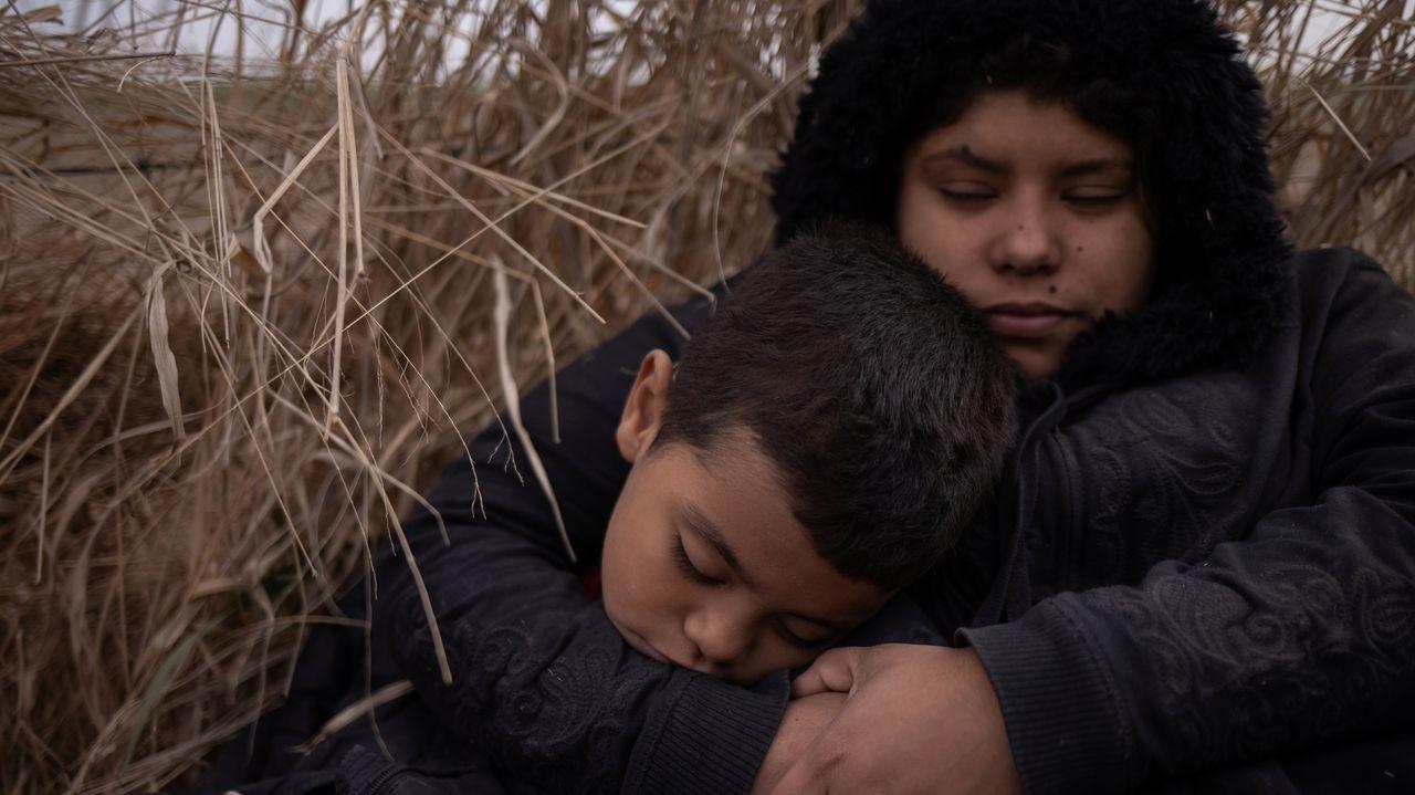 Dos niños migrantes hondureños descansan después de cruzar el Río Grande, en México