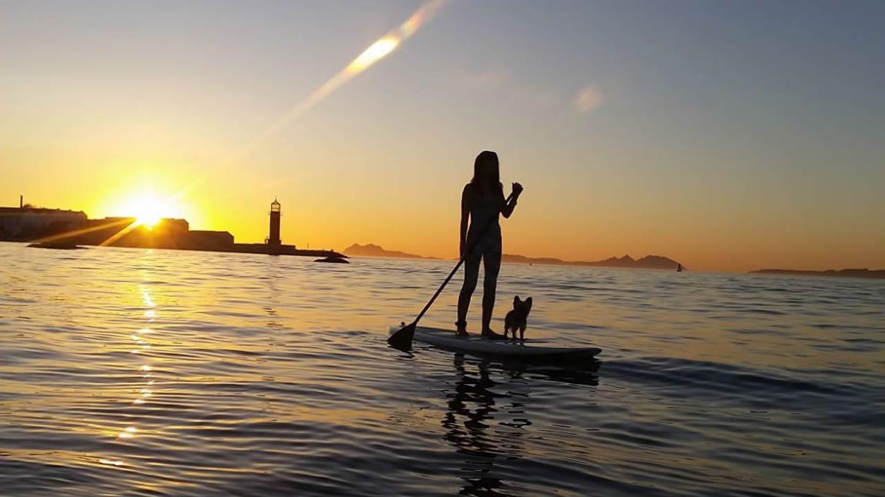 Algunas de las joyas de las Illas Atlánticas.Un perro y su dueña practicando paddle surf en la playa de Bouzas (Vigo)