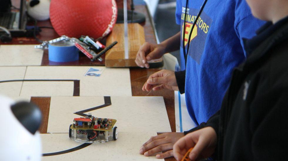 Estes nenos observan nun concurso o robot que eles mesmos fixeron