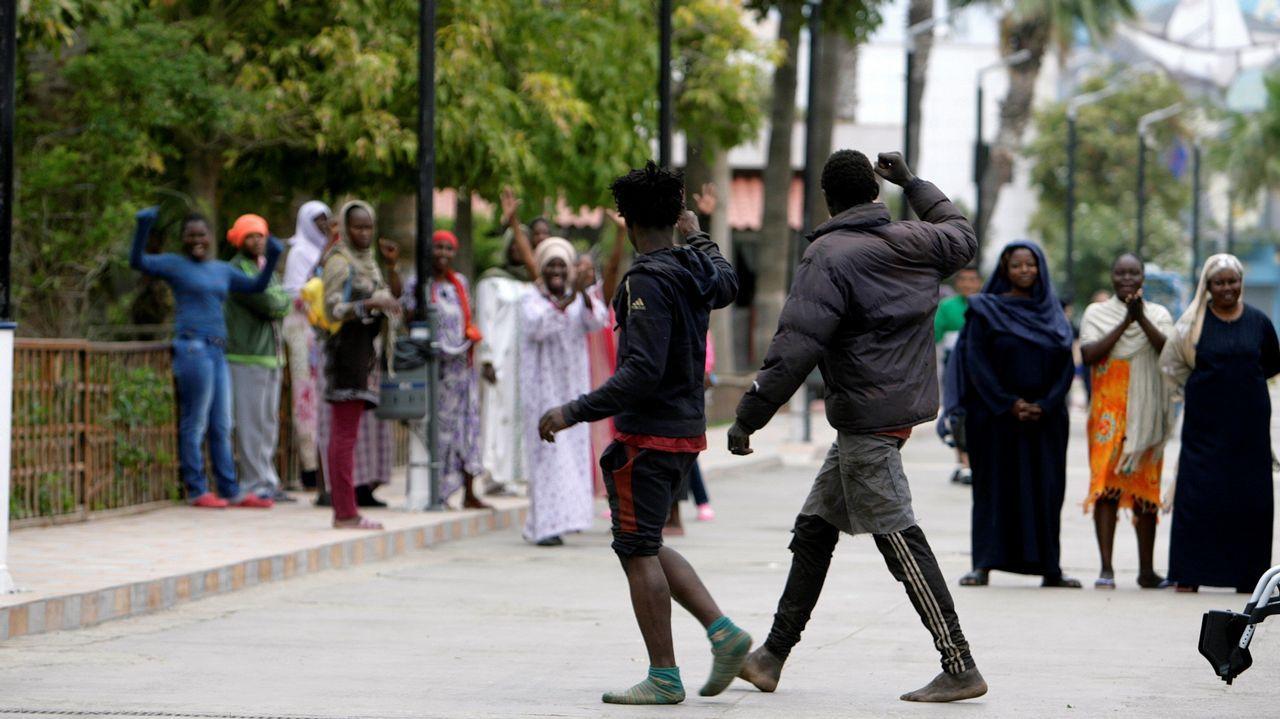 Dos de los 52 inmigrantes que accedieron este domingo a Melilla saltando la valla son felicitados por otros subsaharianos.