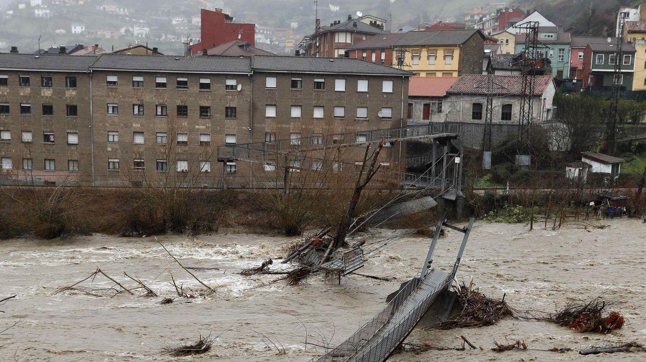 Aspecto que presenta una pasarela peatonal sobre el río Aller a causa del temporal de lluvias registrado en los últimos días en Asturias
