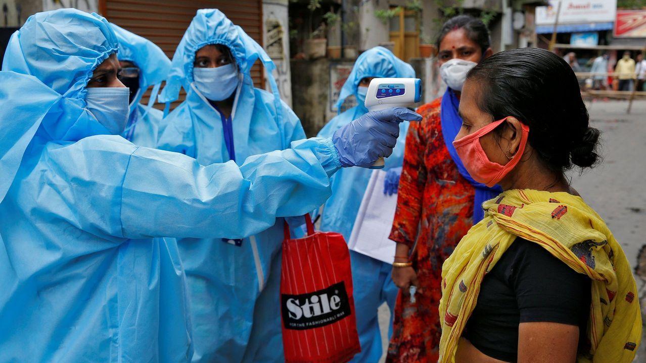 Profesionales sanitarios tomando la temperatura a una mujer en Calcuta