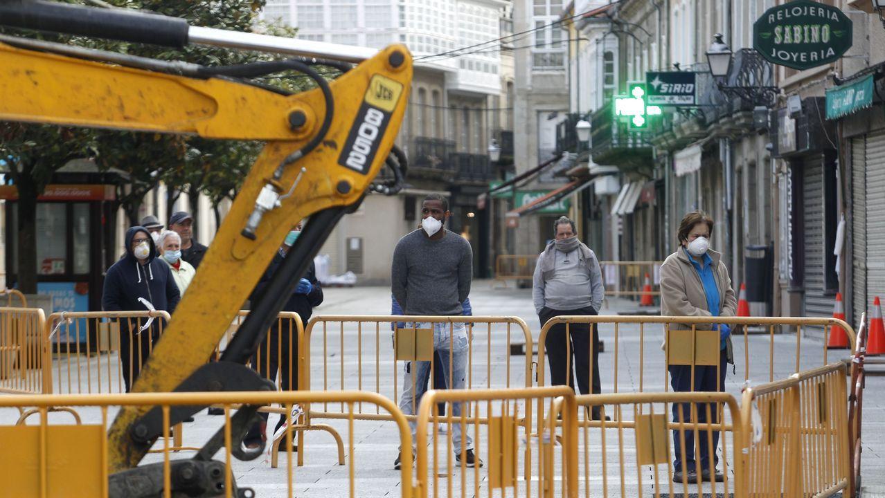 sol, luz, cortinas, ventanas.Clientes de un banco hacen cola para entrar este lunes junto a las obras de la calle Cardenal