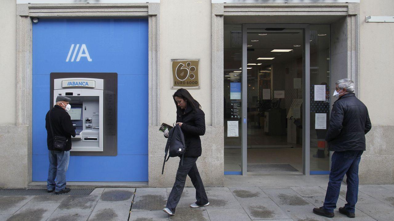 Clientes de un banco con mascarillas, este lunes en el centro de Monforte