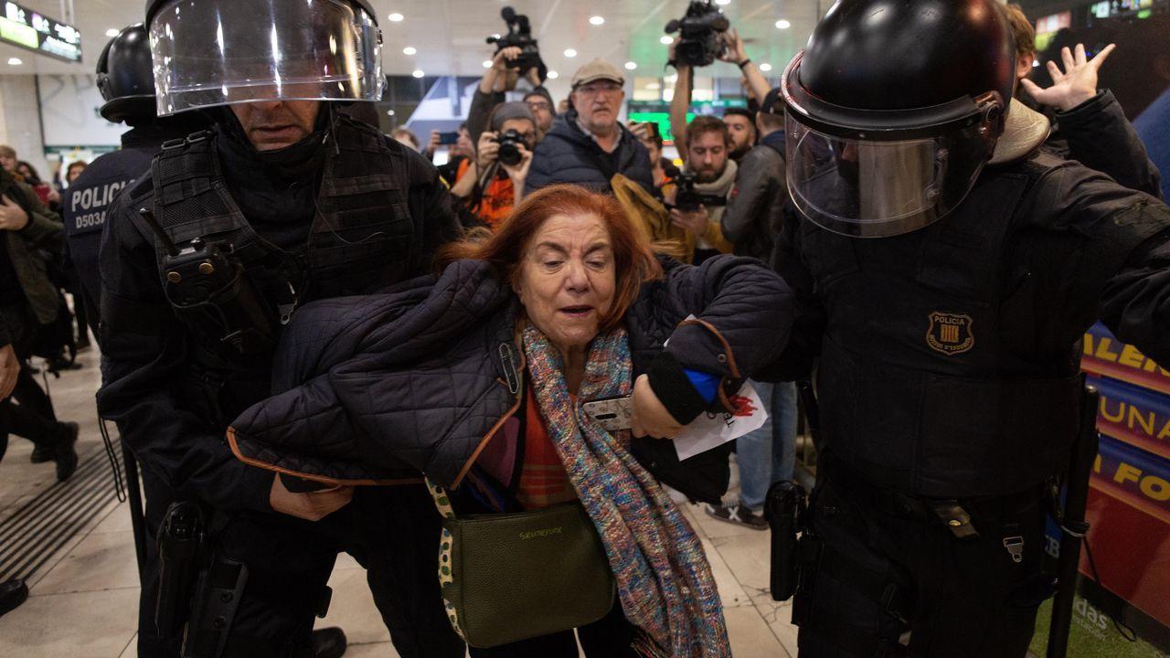 Los Mossos d'Esquadra desalojan a una de las manifestantes del interior de la estación de Sants