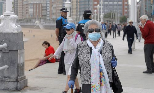 Personas mayores de 70 años pasean por el Muro de San Lorenzo, en Gijón,