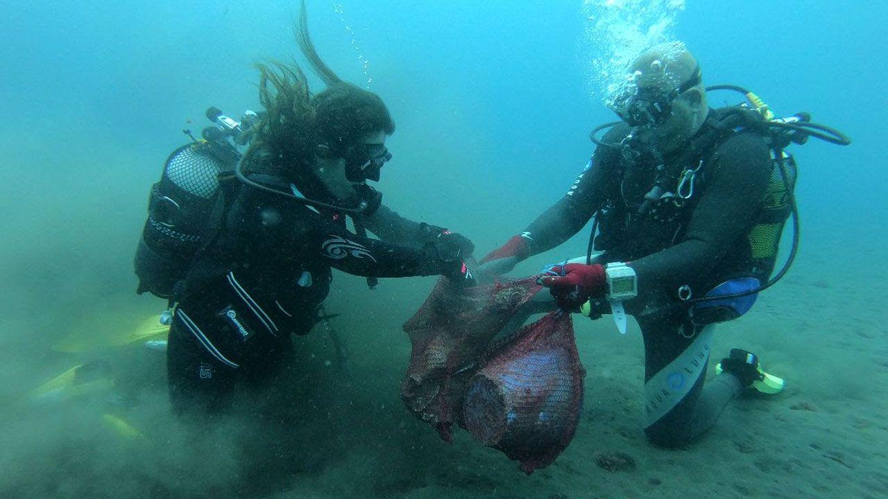 Submarinistas retirando desperdicios del fondo marino