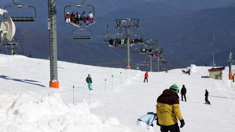 Los esquiadores disfrutan de la nieve con la estación de esquí de Valgrande-Pajares al fondo.Primeras nieves en Valgrande Pajares