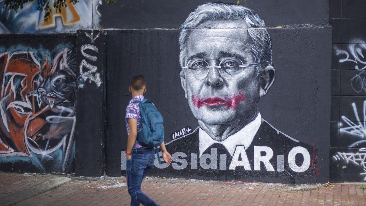 Un hombre observa un mural de uribe en Bogotá