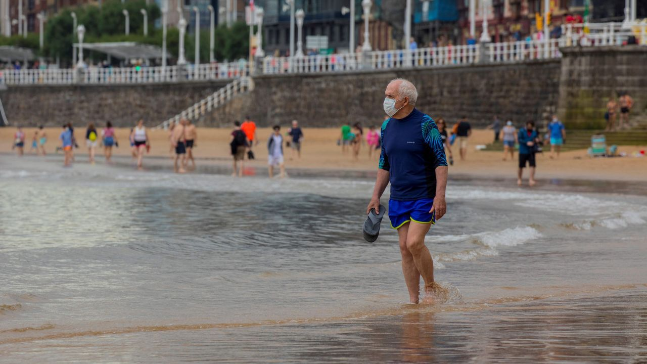 Un hombre camina por la playa de San Lorenzo de Gijón, que en un día nublado