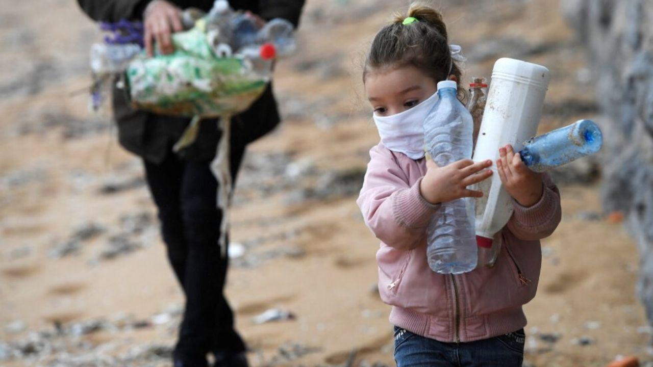 La pequeña Alejandra, de 4 años, el pasado domingo, recogiendo envases de plástico en la playa de San Lorenzo, seguida de su padre, Alexandre