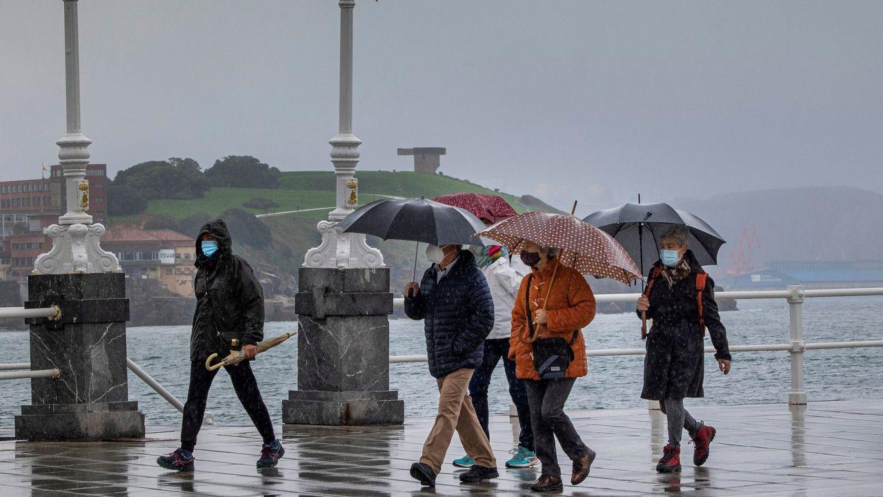 Un grupo de personas paseando por la playa de San Lorenzo ante un tiempo de frío y lluvia