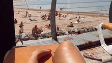 Una gijonesa toma el sol en la playa