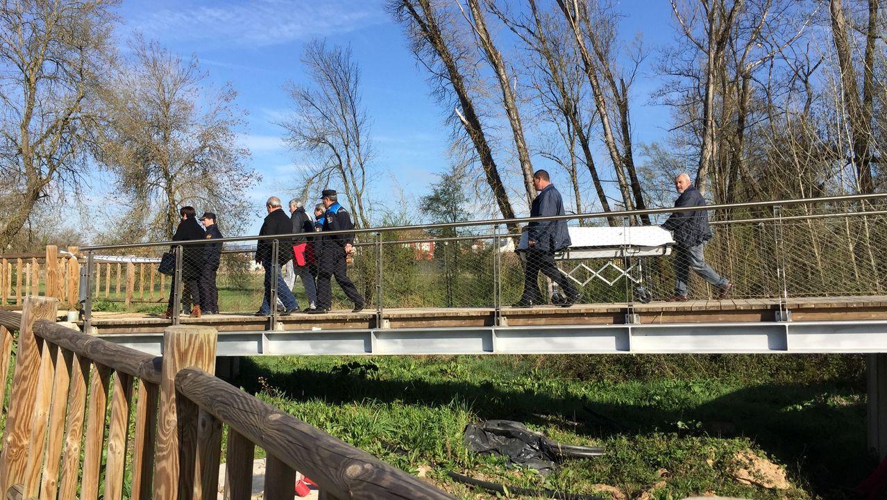 Empleados de una funeraria llevan el cuerpo de la víctima después de que el forense autorizase su traslado