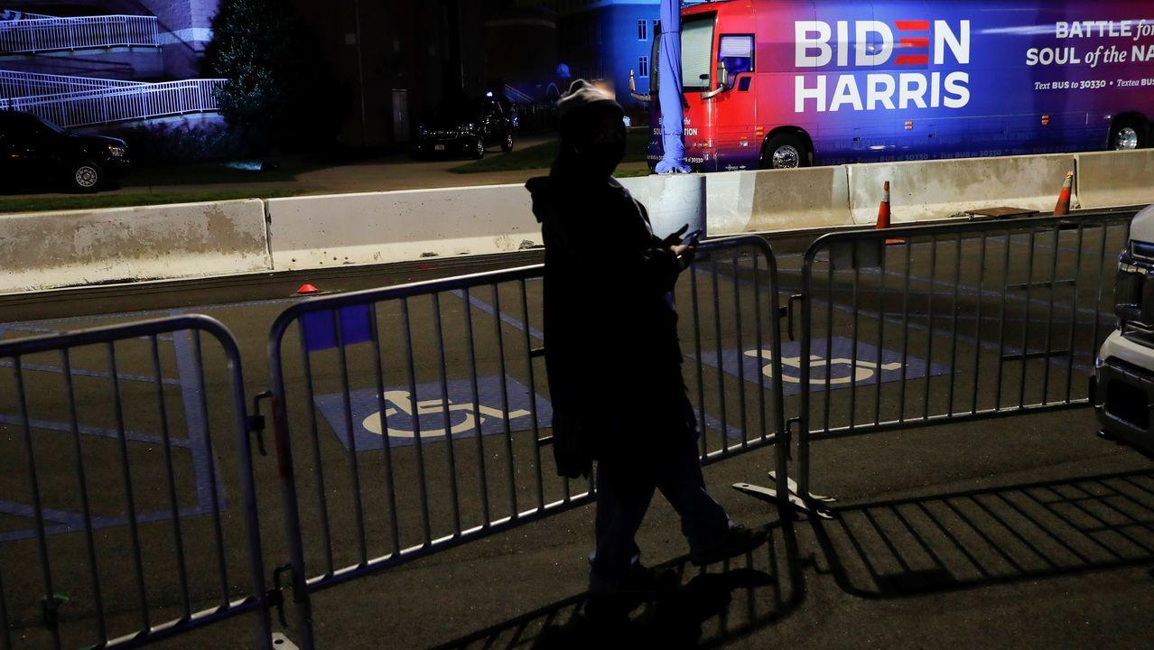 Una mujer pasea por el parking donde Biden celebra su acto público de la noche electoral en Wilmington, Delaware