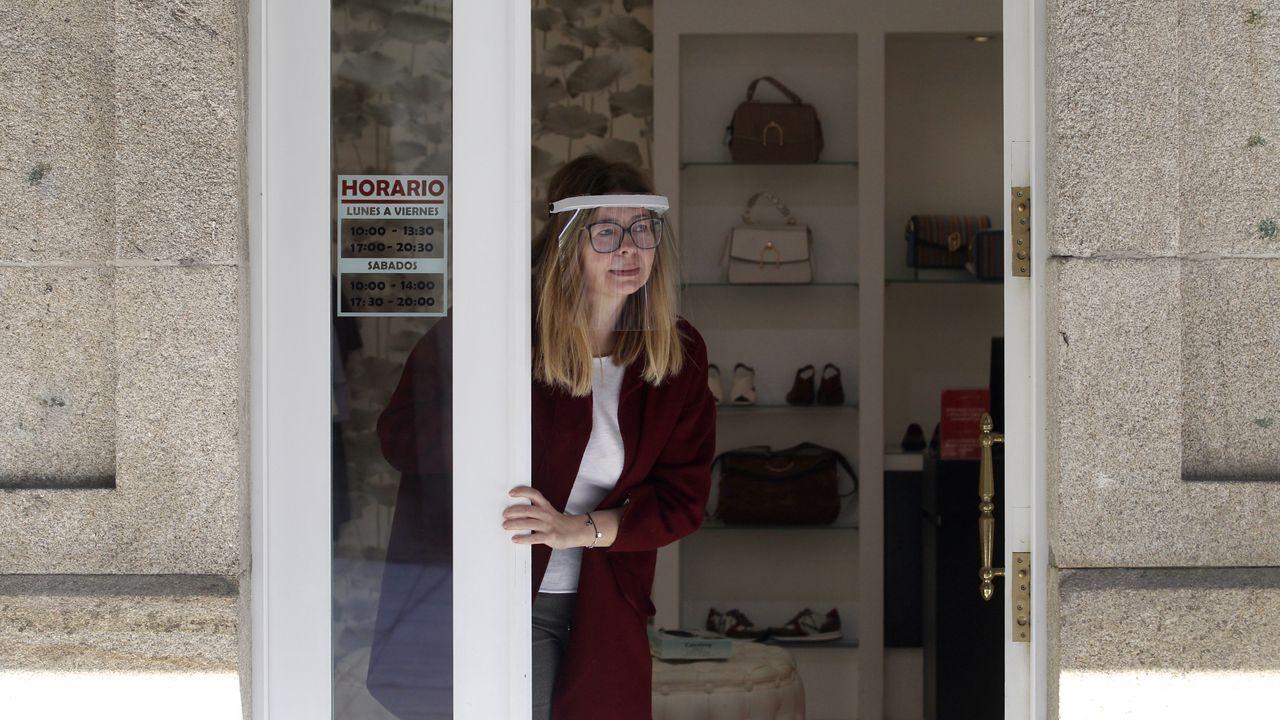 La propietaria de un comercio se asoma a la puerta con una pantalla facial este lunes en el centro de Monforte