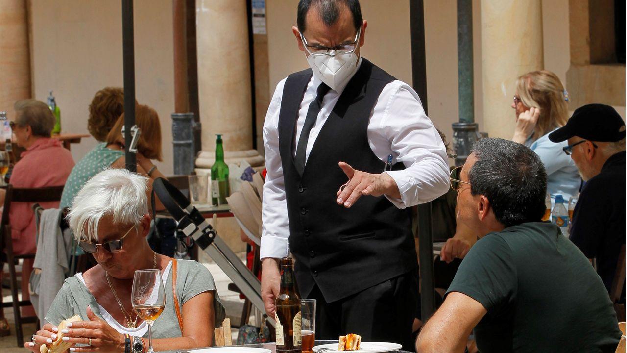 Un camarero atiende a unos clientes en un bar de Oviedo