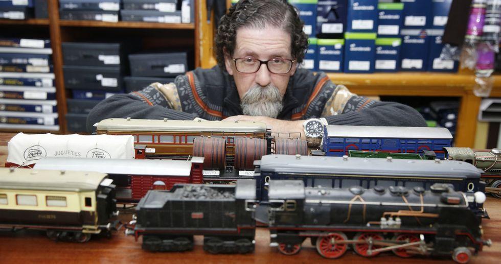 Carlos Díaz González, con algunos de sus trenes y vagones Payá sobre el mostrador de su tienda del centro histórico.