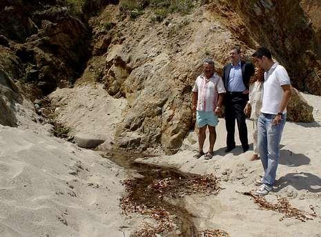Concurso de Castillos de Arena en Barreiros.Miguel Ferreiro y Margarita Varela, en el centro, ante uno de los vertidos denunciados en la playa.