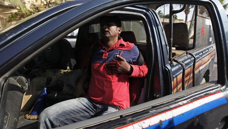 El fotógrafo Asif Hassan se lleva la mano al pecho tras ser alcanzado por una bala