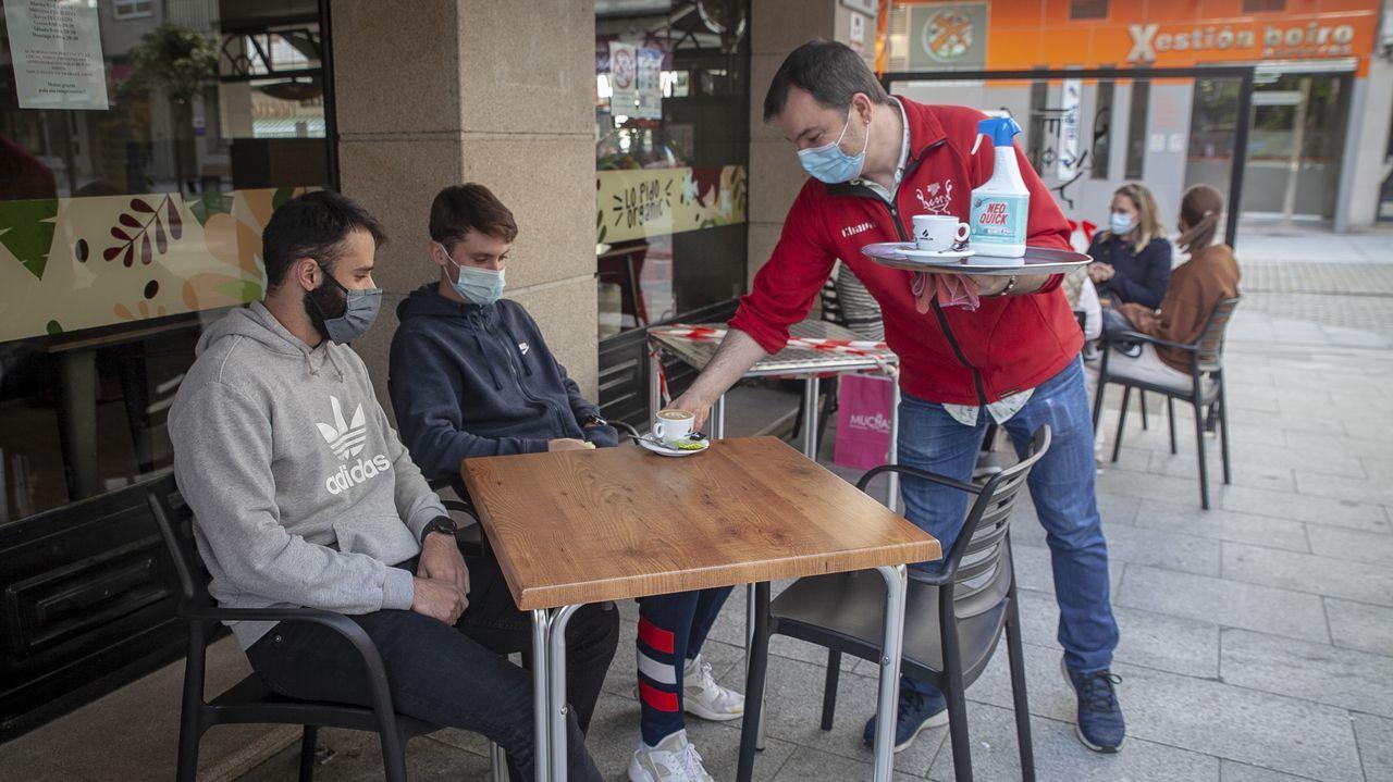 Toni Chaves sirve a unos clientes en la terraza de su cafetería, en Boiro