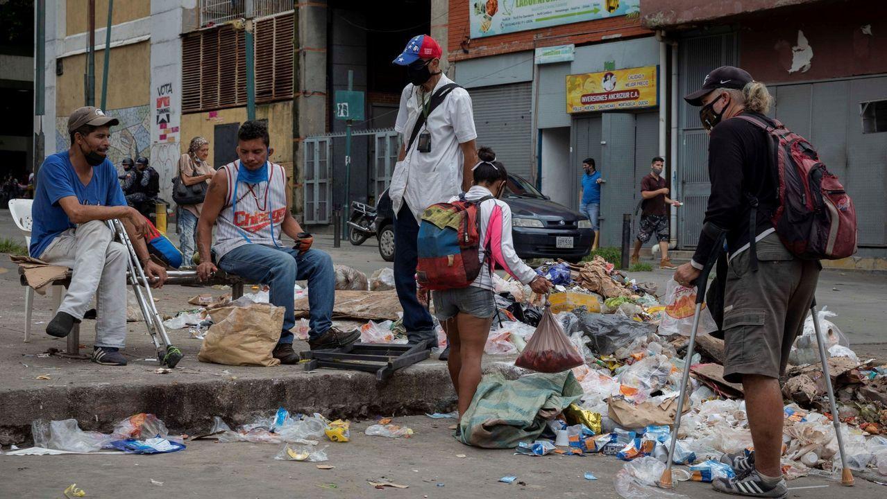 Un grupo de personas escarban entre la basura en una calle de Caracas