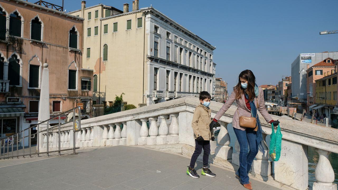 Una madre y su hijo pasean con mascarillas en Venecia
