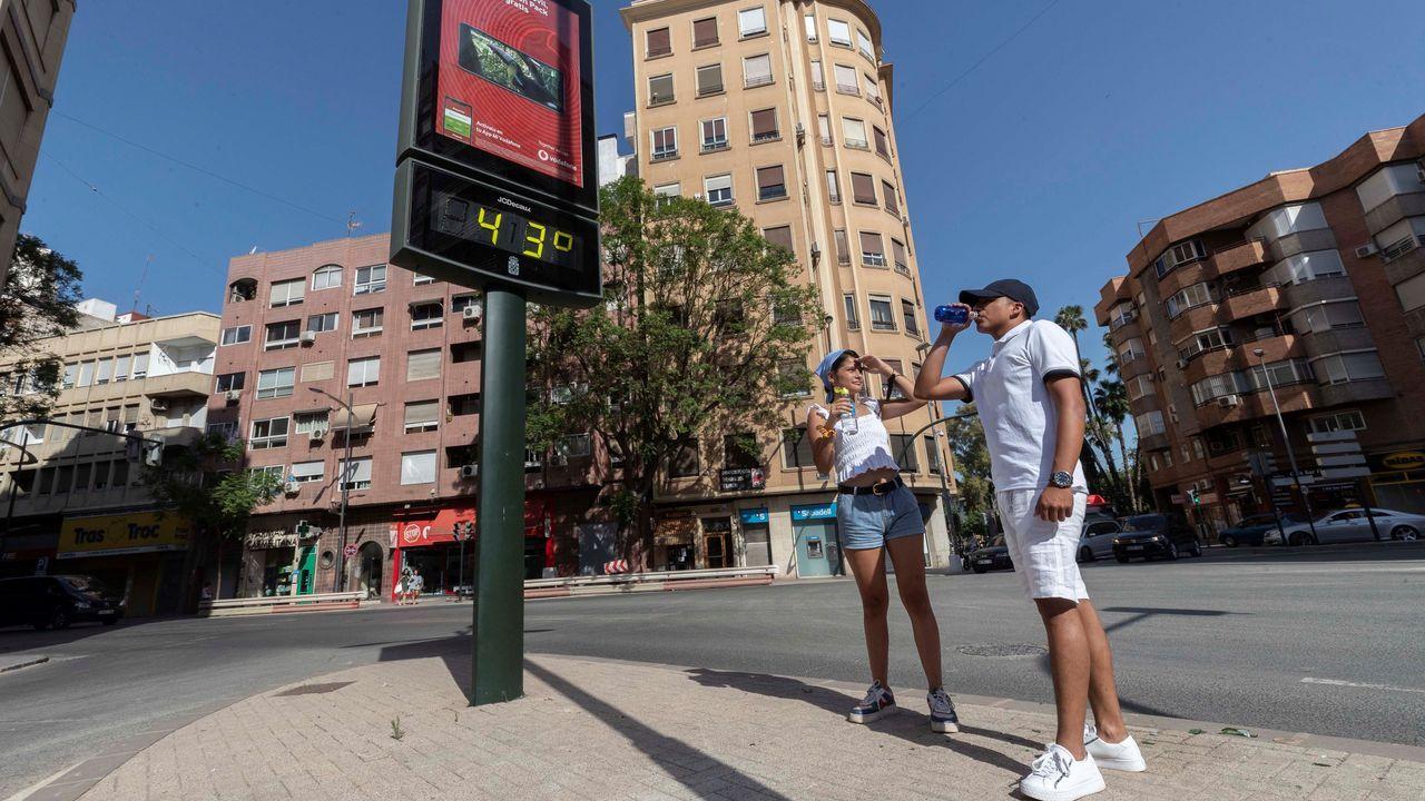 Dos jóvenes beben agua junto a un termómetro que marca 43 grados centígrados, este martes en la Plaza del Royo de Murcia