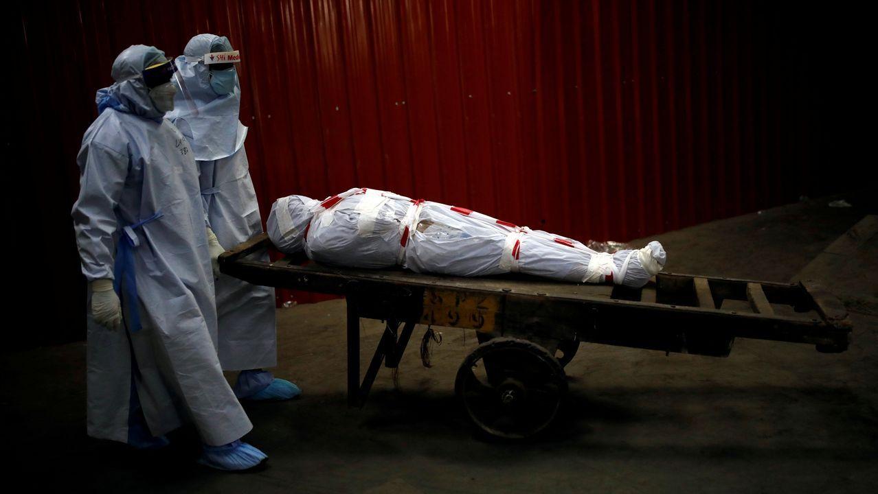Sanitarios portan en Nueva Dehli el cuerpo de un fallecido por covid-19