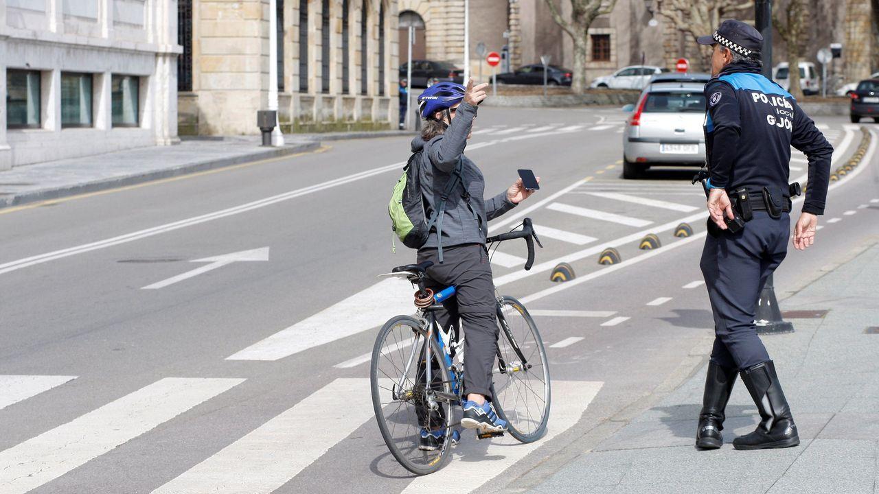 Freddie Mercury se convierte en el protagonista del confinamiento gijonés.Un agente de la Policía Local advierte a una ciclista, en Gijón