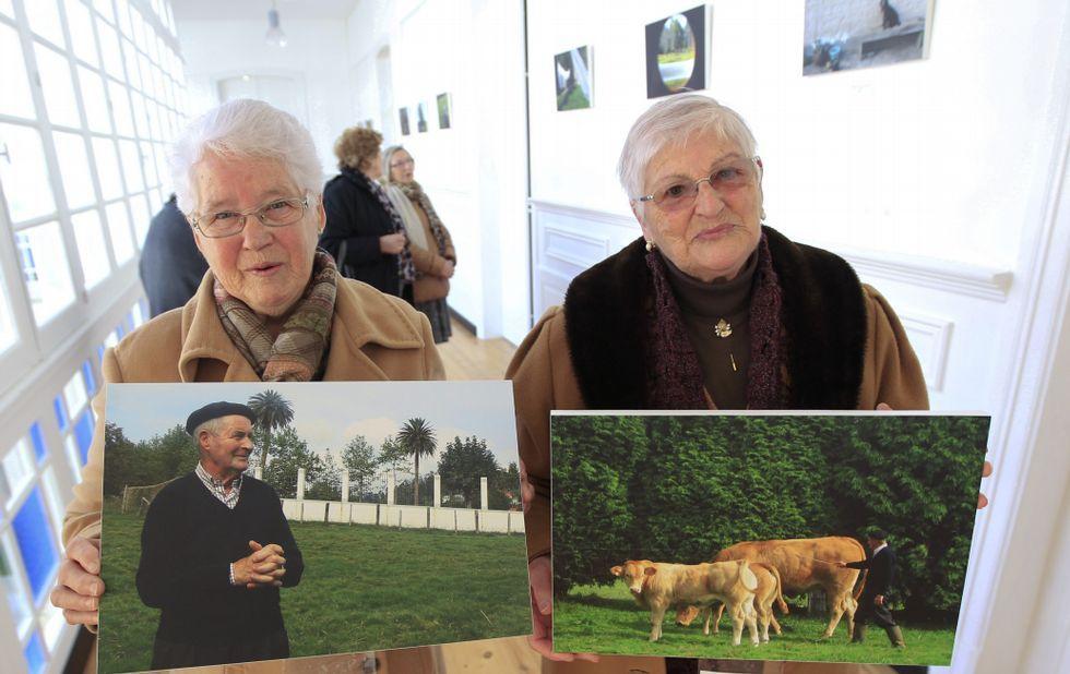 Dos de las fotógrafas, Clara (izquierda) y Marina, muestran sus obras expuestas en el concello.