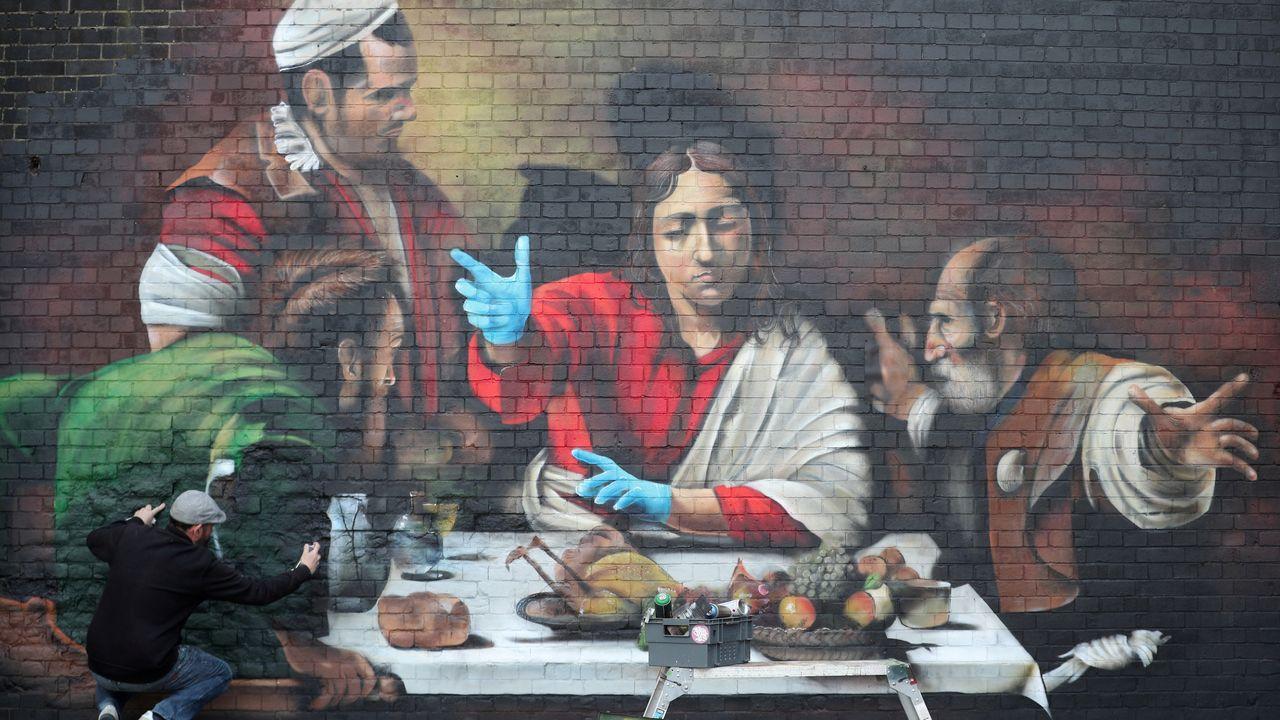 Fin de semana en tiempos de pandemia.El artista Lionel Stanhope realiza un mural en Ladywell, en Londres, que lleva los guantes protectores a la «Cena de Emaús» de Caravaggio