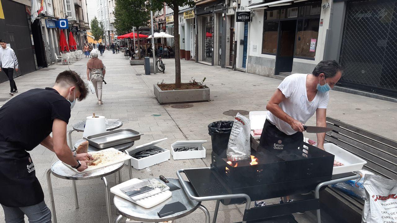 Parrillas de calle en el nuevo San Xoán.Chicho Rodriguez (izquierda) y José Puñal preparan las parrillas en la plaza Elíptica de Los Rosales donde celebrarán el San Xoán