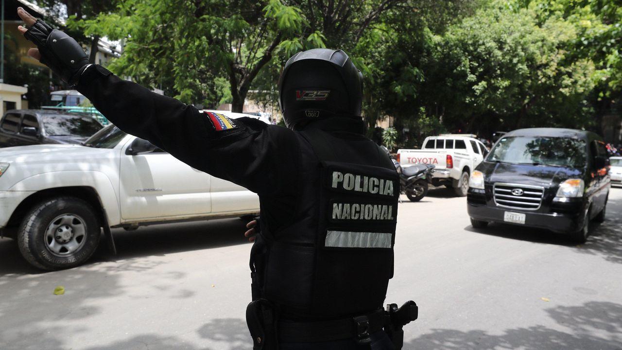 Un policía abre paso al vehículo donde se transportaba el cadáver del capitbán Rafael Acosta Arévalo al cementerio