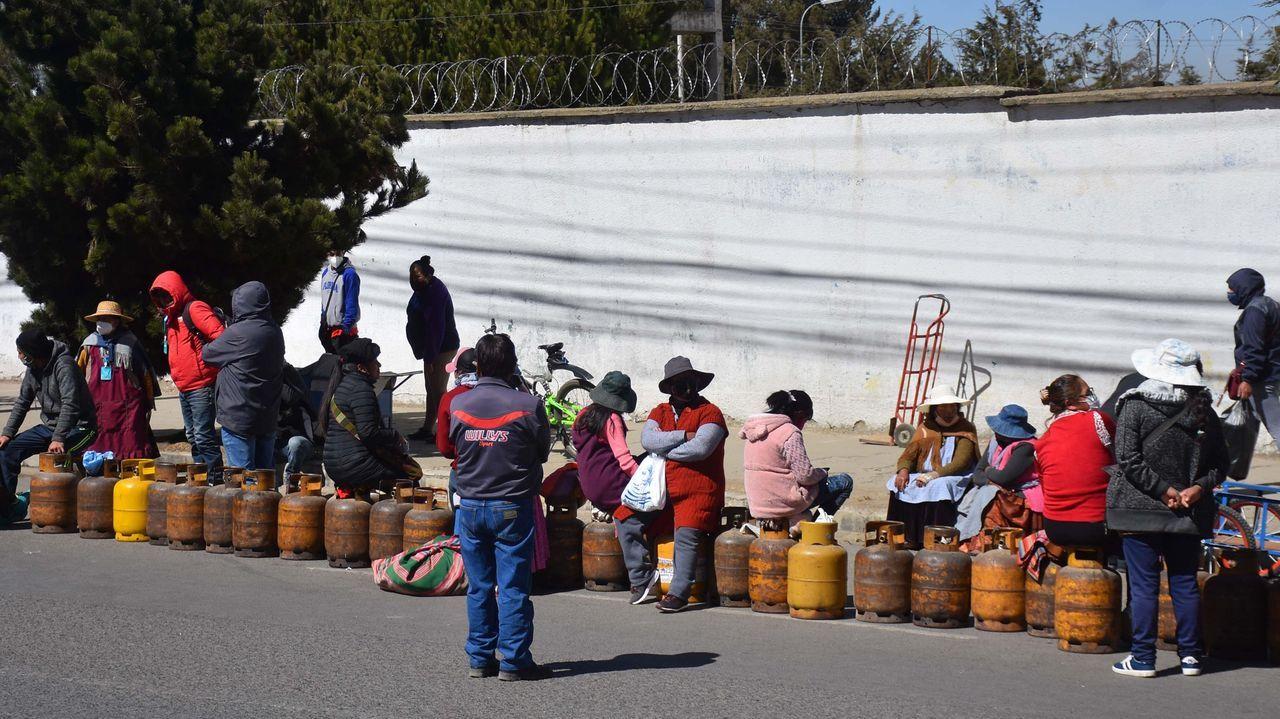 Varias personas esperan en fila para recargar cilindros de gas frente a una planta productora, en El Alto, Bolivia