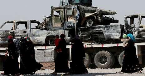 En su huida hacia el Kurdistán, desplazados iraquíes pasan ante restos de vehículos militares en Al Hamdaniya.