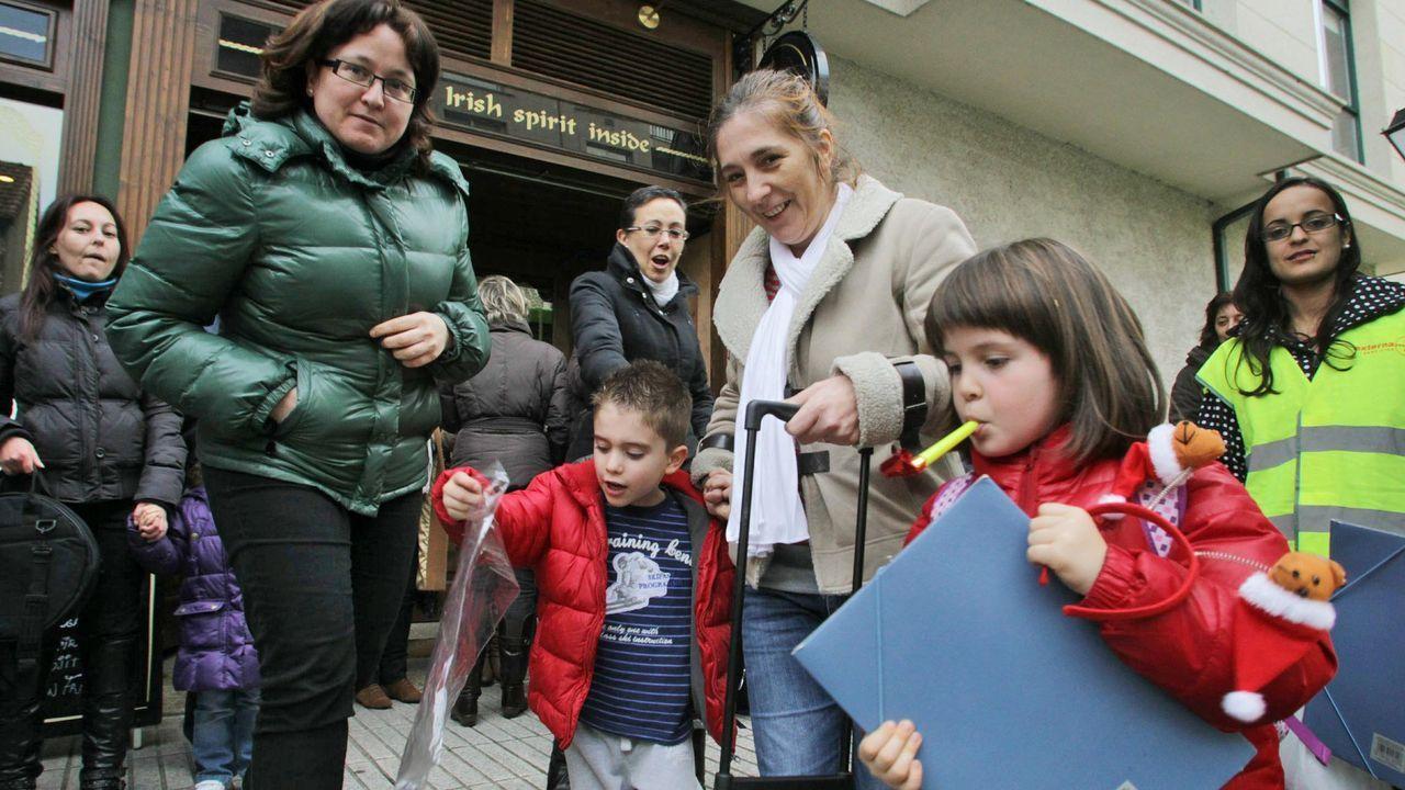 Un grupo de padres recoge a sus hijos, que llegan en el autobús escolar del colegioo de Ventín de O Milladoiro